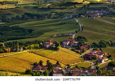 View from above on green vineyards and small town on the hills of Piedmont, Northern Italy.