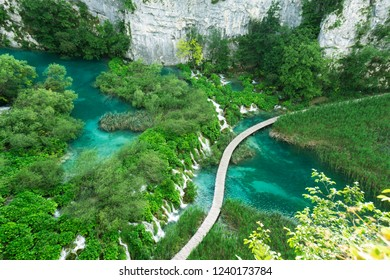 View from above on the hiking path in Plitvice Lakes National Park, Croatia. Beautiful landscape, clear water and wooden pathways that lead to amazing waterfalls.