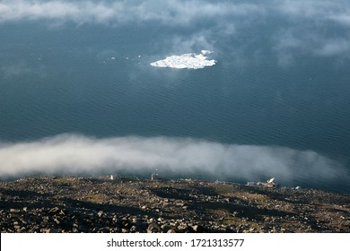 View from above on iceberg in Arctic ocean, floating clouds and weather station in Chukotka, Far East Russia