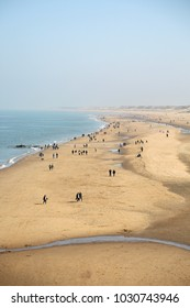 A view from above on the ocean coast among the dunes on a sunny and clear day, where people walk along the beach.
