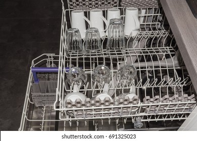 View from above on an open dishwasher with clean cup, glasses and plates.