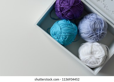 View from above on purple, blue and white knitting yarn wools in wooden box with a copy space on white background.