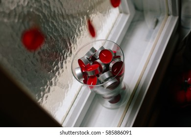 View from above on red heart shaped string lights and a glass vase full of red tea light candles in between window frames.