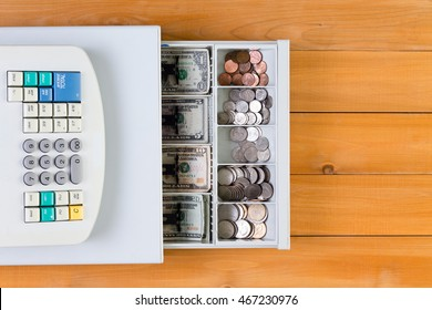 View from above on retail business cash register full of coins and bills over yellow stained wooden table
