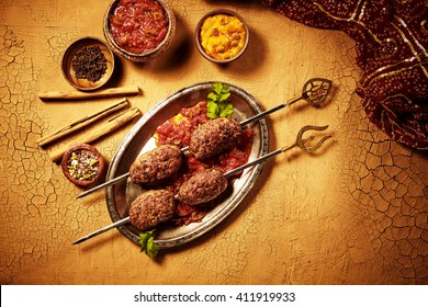 View from above on shish kebab meat Indian meal in metal plate with sauces and spices with dried bamboo sticks on cracked paint surface