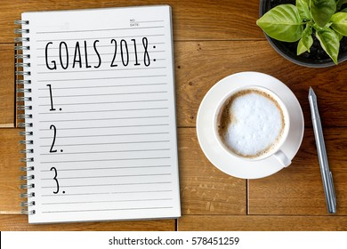 View from above on the table with a notebook and goals for 2018 year
