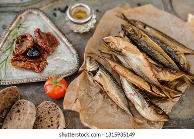 View from above on the tasty smoke-dried horse mackerel fish on the paper with a sun dried and fresh tomatoes, oil and bread on the metal background.