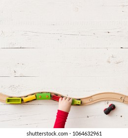 View from above on toy wooden trains on railway. Child's hands playing with educational toy - train