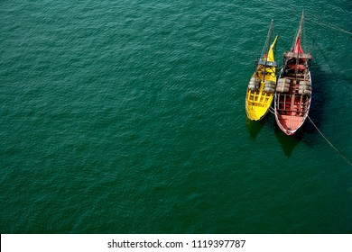A view from above on two boats, red and yellow which are located on the blue water, the river. Porto, Portugal.