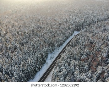View from above on a winter forest with a road going through
