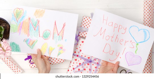 View from above on woman's hands holding handmade greeting cards for mother's day. Happy Mother's day celebration concept