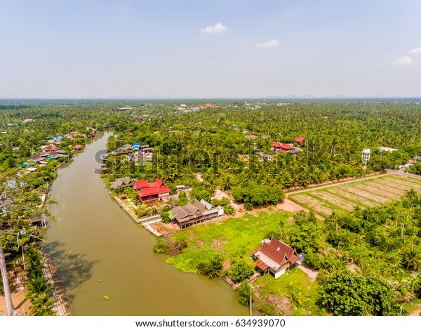 The view from above of the orchards land and houses along a canal in Samut Songkram province of Thailand
