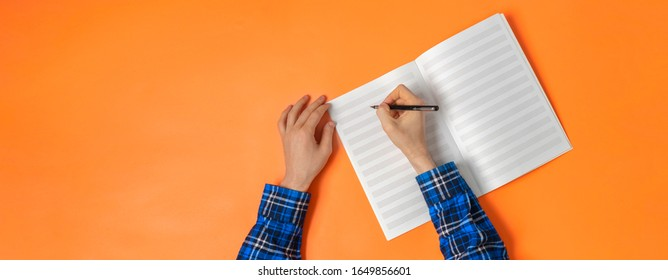 a view from above, person taking down the notes in notebook, empty blank paper mockup with copy space