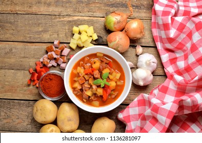View from above of potato and sausage goulash, pepper, onion and garlic on wooden table and red dish-cloth