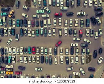 A view from above to the process of car parking. Heavy traffic in the parking lot. Searching for spaces in the busy car park. Parking advice. Cruising for parking in busy business center.