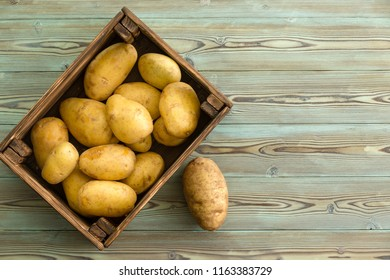 View from above rectangular dark wood container of delecious fresh potatoes sitting on wooden table
