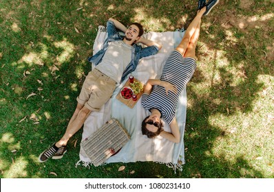 View from above of relaxed man and woman lying down at the park with hand basket, appetizing snacks and beers on blanket. Couple on picnic lying on blanket in grass outdoors.