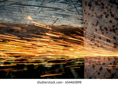 A view from above of sparks flying from a metal plate. a circular saw. copyscape