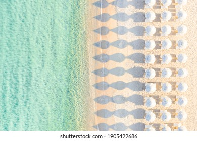 View from above, stunning aerial view of an amazing empty white beach with white beach umbrellas and turquoise clear water during sunset. Mediterranean sea, Sardinia, Italy.