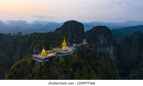 View from above, stunning aerial view of the beautiful Tiger Cave Temple (Wat Tham Sua) surrounded by amazing ridges of limestone mountains during the sunset. Krabi, Thailand.