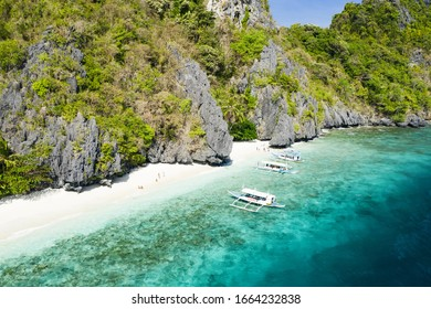 View from above, stunning aerial view of the Entalula Beach, a white sand beach bathed by a crystal clear sea. Entalula island, Bacuit Bay, El Nido, Palawan, Philippines.