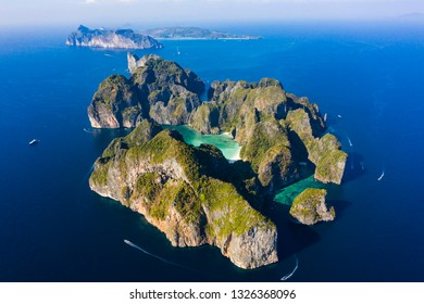 View from above, stunning aerial view of Koh Phi Phi Lee with the beautiful beach of Maya Bay bathed by a turquoise clear water. Amazing limestone karst formations surround this island in Thailand.