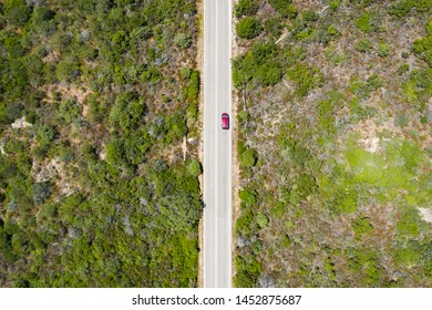 View from above, stunning aerial view of a red car that runs along a road flanked by a green forest. Sardinia, Italy.