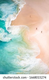 View from above, stunning aerial view of some people relaxing on a beautiful beach bathed by a turquoise sea during sunset. Kelingking beach, Nusa Penida, Indonesia.
