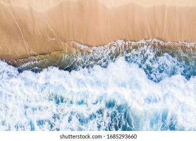 View from above, stunning aerial view of waves crashing onto a beautiful beach during a sunny day. Nyang Nyang Beach (Pantai Nyang Nyang), South Bali, Indonesia.