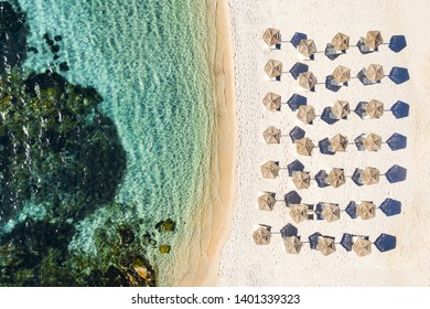 View from above, stunning aerial view of a white beach with beach umbrellas and turquoise clear sea. Emerald Coast (Costa Smeralda), Sardinia, Italy.