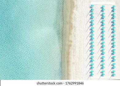 View from above, stunning aerial view of a white sand beach with beach umbrellas and a beautiful turquoise sea. Marinella Beach, Porto Rotondo, Costa Smeralda, Sardinia, Italy.