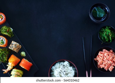 View from above of stylish japanese meal over dark board with a copy space. Variety of sushi rolls with salmon, shrimp, wakame and avocado, bowl of rice, crab meat, wakame salad and cup of green tea.