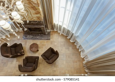 View from above of  stylish living room with fireplace and armchairs around. Interior in brown, beige and golden colors with elements of wood and dark granite. Room with big windows.