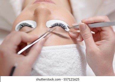 View from above of stylist holding tweezers and tongs and making lengthening lashes for women in a beauty salon. Professional making eyelash extension. Female lying with closed eyes.