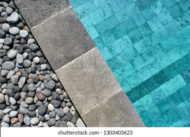 View from above at a swimming pool with blue water outdoors. It has a tiled gray edge which is decorated with pebbles. Closeup horizontal photo..