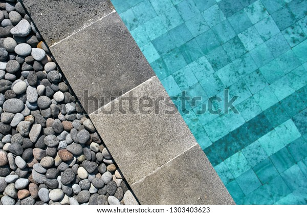 Blick von oben auf ein Schwimmbad mit blauem Wasser im Freien. Es hat einen grauen Fliesenrand, der mit Kieselsteinen verziert ist. Nahaufnahme eines horizontalen Fotos..