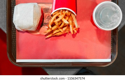View from above of a tray served with a burger fries and soda combo