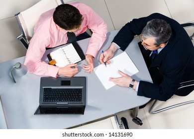 View from above of two businessmen speaking in the office during meeting