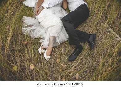 View from above of two newlyweds lying on the grass embracing each other.