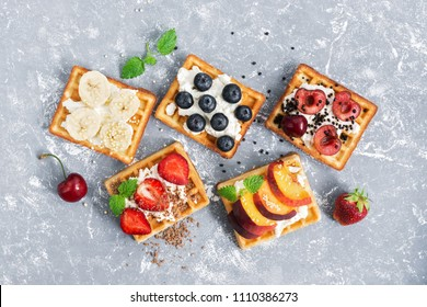 A view from above of a wafer with a cream of fruit and berries on a gray background. Traditional Belgian waffles