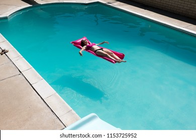 View from above of woman floating on a bright pink raft in an outdoor swimming pool. Caucasian girl in bikini on holiday lounging in swimming pool in the sun on a pink raft. Resting, getaway.