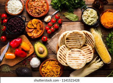 View from above of a wooden rustic table with several ingredients for cooking and filling arepas, typical Latin American food.