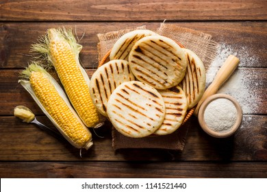 View from above of wooden rustic table with several ground corn Arepas, some corn and butter. Venezuelan traditional cuisine