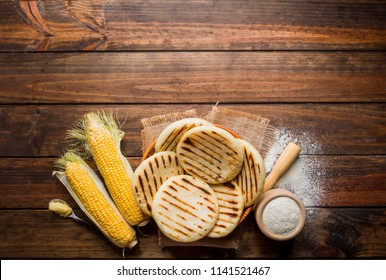 View from above of wooden rustic table with several ground corn Arepas, some corn and butter. Venezuelan Food