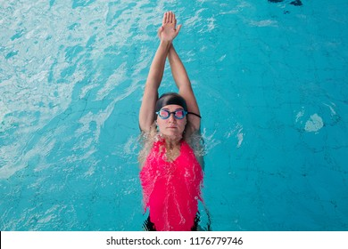 View from above of young sporty girl in goggles and cap swimming in the blue water pool. Woman concentrated swimming forward, wearing in pink swimsuit, engaged in sports. Concept of water sport.