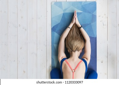 View from above of young woman working out at home on white wooden floor, doing yoga exercise on blue mat, relaxing and meditating after practice