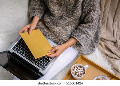 View from above.Golden envelope in female hands. Girl,dressed in knitted sweater,sitting on white furry rug and using laptop.Near smartphone,on tray cup of cocoa with marshmallows,jar of biscuits.
