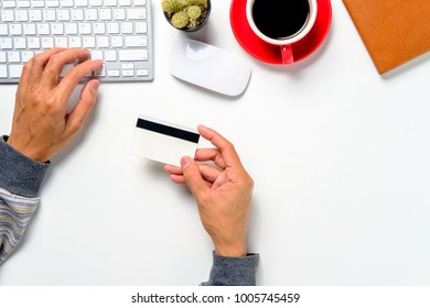 View from above.Hipster man hands holding a credit card and using smart phone for online shopping.Online shopping concept.