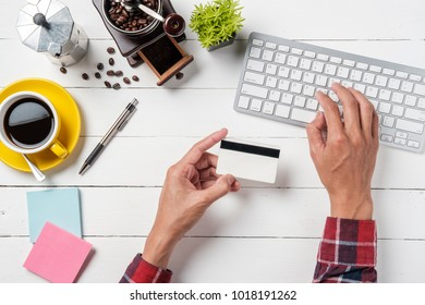 View from above.Hipster man hands holding a credit card and using computer for online shopping.Online shopping concept.