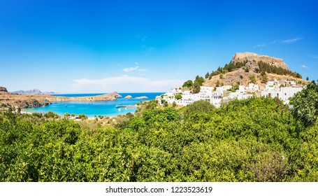 View of Acropolis of Lindos, traditional white houses and lemon trees (Rhodes, Greece)
